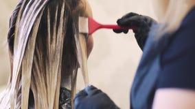 Stilistfriseur macht die Haarfärbung und blonding Sie benutzt die Bürste Nahe Ansicht Friseur ` s Hände in den schwarzen Handschu stock video footage