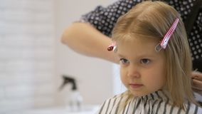 Stilistfriseur macht eine Frisur für ein nettes kleines Mädchen in einem Schönheitssalon Frisur, Haarausschnitt stock video footage