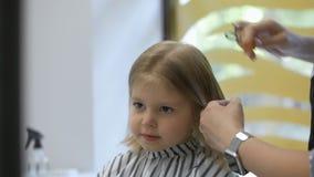 Stilistfriseur macht eine Frisur für ein nettes kleines Mädchen in einem Schönheitssalon Frisur, Haarausschnitt stock footage