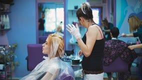Stilistfriseur tut eine Berufsfarbe auf dem Haar seines Kunden stock video