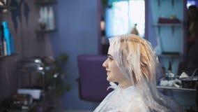 Stilistfriseur tut eine Berufsfarbe auf dem Haar seines Kunden stock footage