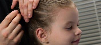 Stilistkapper creeert een kapsel voor de avond, een klein meisje, stekenhaar met een haarspeld royalty-vrije stock foto's
