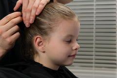 Stilistkapper creeert een kapsel voor de avond, meisje, stekenhaar met een haarspeld, babyglimlachen royalty-vrije stock afbeelding