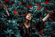 Stilkvinnan n?ra rhododendronblommor i a grarden royaltyfri fotografi