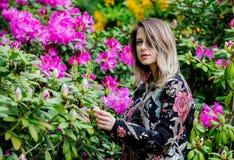 Stilkvinnan n?ra rhododendronblommor i a grarden arkivfoto