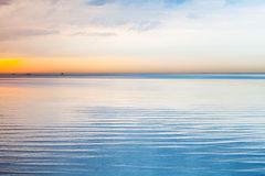 Still blue sea water under colorful sky. Still blue sea water under colorful evening cloudy sky Stock Images