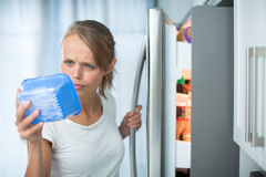 Is this still fine? Pretty, young woman in her kitchen by the fr Stock Photography