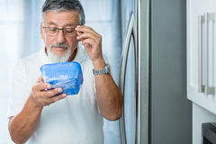 Is this still fine? Senior man in his kitchen by the fridge Stock Photo