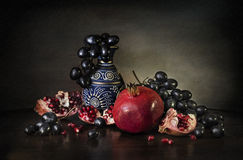 Still garnet grapes and pitcher. Still Life with a red garnet and black grape with ancient oriental pitcher royalty free stock photo