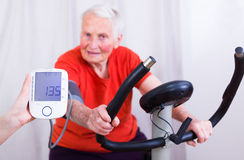 Still got it. Elderly woman doing sport effort on a spinning bike having hear hart rate and blood pressure monitored Royalty Free Stock Photos
