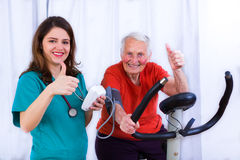 Still got it. Elderly women doing sport effort on a spinning bike having hear hart rate and blood pressure monitored royalty free stock image