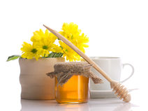 Still of honey, flowers and teacup. Still of honey, drizzler, flowers and teacup isolated on white royalty free stock photography