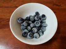 Still image of frozen fresh blue berries in white bowl Stock Photos