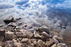 Still lake coast, coastal stones and blue cloudy sky Royalty Free Stock Photos