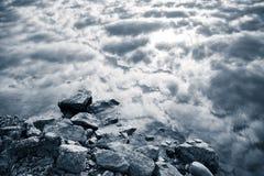 Still lake coast, stones and cloudy sky, monochrome Stock Photos