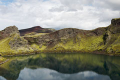 Still lake in a crater with reflections on a sunny day, Iceland Stock Photos