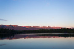 Still Lake with Sun Setting Over Distant Mountains. Incredible still and calm Boya Lake in Canada as orange/purple sunset colours are projected onto the Stock Image