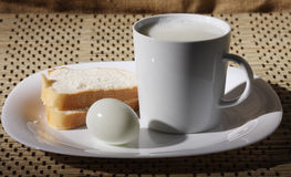 Still life. Dish. On dish cup with milk, bread and egg. Still life Stock Photo