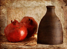 Still life. Photo of an still life of pomegranate on fan and vase old stylized Royalty Free Stock Photography