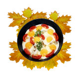 Still-life. Frying pan with fried eggs on yellow autumn leaves Stock Photos