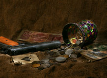 Still life. With gun,old money, cards and vase on a dark background royalty free stock photography