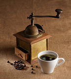 Still life. Cup of coffee, grinder, and coffee beans on brown background stock photo
