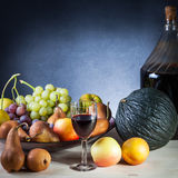 Still life. Of various fruits and a glass of wine on a wooden table with blue background Royalty Free Stock Photo