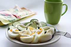 Still-life. Cut cucumbers and eggs on plate, near cup of green color and a pack of mayonnaise Stock Photo