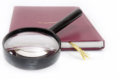 Still-life 7. The lens lays on the book Stock Images