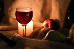 Free Still Life. A Glass Of Red Wine And Candle Light Behind It On Table In A Half Light With Fruits On Sackcloth Background Royalty Free Stock Image - 163510286