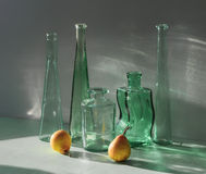 Still Life Accent. Five-transparent bottles and two yellow pears stock image