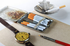 Still life with an ancient cigarette case. Still life with a cigarette case, hours and cigarettes in a retro style Stock Images