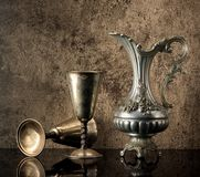 Still life with Ancient jug for wine and silver goblets royalty free stock photo