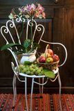 Still life with antique chair, flowers and fruit Stock Photo