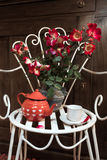 Still life with antique chair, flowers and tea Stock Images