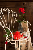Still life with antique chair, flowers and tea Stock Photo