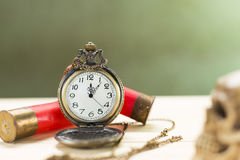 Still life antique clock. Placed on a wooden floor and a red shotgun shell with human skull on the back Royalty Free Stock Photos