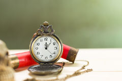 Still life antique clock. Placed on a wooden floor and a red shotgun shell with human skull on the back Stock Photo