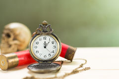 Still life antique clock. Placed on a wooden floor and a red shotgun shell with human skull on the back Royalty Free Stock Photo