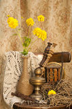 Still life. With antique clockwork, oil lamp and yellow flowers Stock Images