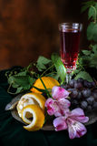 Still life in antique style with a glass of wine, grapes and two Stock Photos