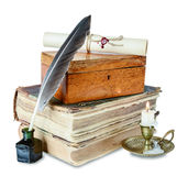 Still life with antiques. Old books, candle in candlestick, feather in inkpot, closed wooden box and scroll with stamp Stock Photo