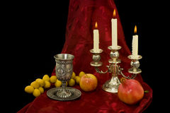 Still-life with an apple, dates and a pomegranate. Still-life with a candlestick, a glass for wine, an apple, dates and a pomegranate on a red-black background Stock Photography