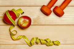Still Life apple, dumbbells and tape measure Royalty Free Stock Images