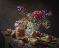 Still life with apple jam. In a glass jar, opoyasonnoy pink ribbon and lace paper, amber, as well as with jam in kremanke with a spoon in a vintage style, with stock photography