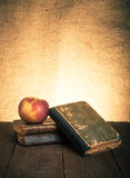 Still life with apple and a stack of old books on old wooden tab Royalty Free Stock Images