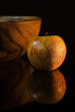 Still-life with apple and wooden dish Stock Images