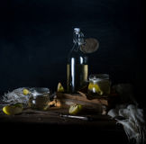Still life with apples, apple juice, old books and a silver knife on a wooden table on a dark background. vintage Royalty Free Stock Images