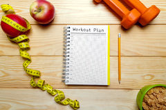 Still life of apples, dumbbells, flakes and notebook and tape me Stock Photography