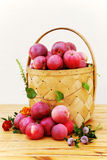 Still life with apples, flowers and basket. Red autumn apples in a basket made of birch bark Royalty Free Stock Photography